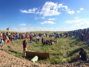 Wide circle of water protectors at one end of Dakota Pipeline